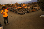 A homeowner, wishing not to be identified, stands in front of his fire-ravaged home Saturday, Sept. 19, 2020, after the Bobcat Fired passed through in Juniper Hills, Calif. (AP Photo/Marcio Jose Sanchez)
