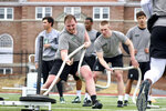 In this March 29, 2018, photo, Dartmouth College defensive lineman Seth Simmer, foreground, pulls a weighted sled during  NCAA college football conditioning drills on Memorial Field in Hanover, N.H. Kent State receiver Antwan Dixon, Dartmouth defensive lineman Seth Simmer and Carson-Newman running back Antonio Wimbush are the first recipients of the Mayo Clinic college football Comeback Player of the Year Award. The new award recognizes college football players from FBS, FCS and lower divisions who overcome injury, illness or other challenges to return to the field. (Tris Wykes/The Valley News via AP)
