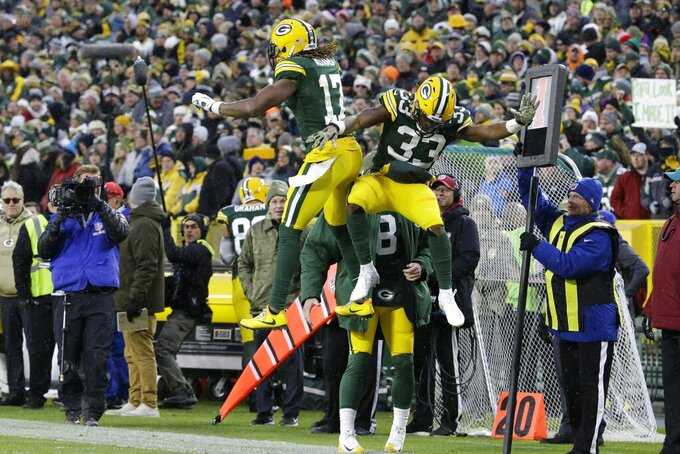 Green Bay Packers' Aaron Jones celebrates his touchdown run with Davante Adams during the first half of an NFL football game against the Carolina Panthers Sunday, Nov. 10, 2019, in Green Bay, Wis. (AP Photo/Mike Roemer)