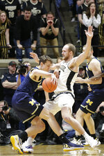 Michigan guard Franz Wagner (21) dribbles against Purdue forward Evan Boudreaux (12) during the first half of an NCAA college basketball game, Saturday, Feb. 22, 2020, in West Lafayette, Ind. (Nikos Frazier/Journal & Courier via AP)
