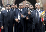 Mohammad Azhar Siddique, center, a lawyer for former Pakistani President and military ruler Pervez Musharraf, and other lawyers make a victory sign after a court decision, in Lahore, Pakistan, Monday, Jan. 13, 2020. The Pakistani court Monday overturned a death sentence given to the country's ailing former dictator, saying a special court that last month convicted and sentenced Musharraf had been formed in violation of the law. (AP Photo/K.M. Chaudary)