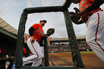Baltimore Orioles first baseman Chris Davis, left, trots out of the dugout during a spring training baseball game against the Atlanta Braves, Tuesday, March 10, 2020, in Sarasota, Fla. (AP Photo/Elise Amendola)
