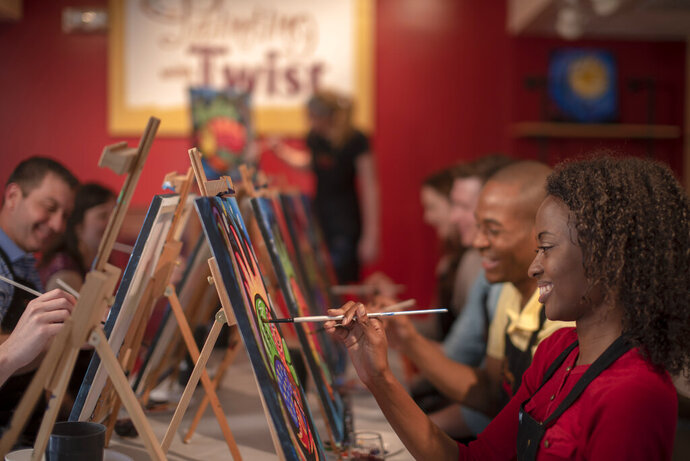 This 2019 photo provided by Painting with a Twist shows a group taking part in a Painting with a Twist event in Mandeville, La. In recent years, the interactive painting industry has become a global sensation. Around the world, adults can spend their nights out learning to paint in a relaxed, BYOB setting. Thousands of franchises exist to help us all unleash our inner creative. (Painting with a Twist via AP)