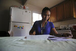 Mary Taboniar, a housekeeper at the Hilton Hawaiian Village resort in Honolulu, looks over bills at her home in Waipahu, Hawaii, Saturday, Sept. 4, 2021. Taboniar went 15 months without a paycheck, thanks to the COVID pandemic. The single mother of two saw her income completely vanish as the virus devastated the hospitality industry. Taboniar is one of millions of Americans for whom Labor Day 2021 represents a perilous crossroads. (AP Photo/Caleb Jones)