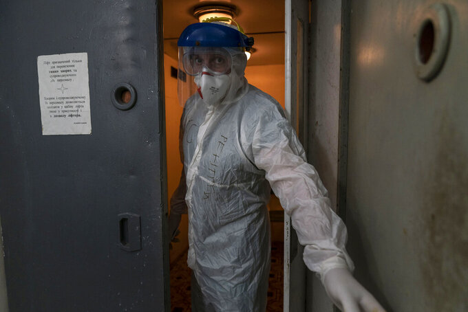 Dr. Oleh Hornostayev closes an elevator door going into a red zone at the city hospital in Stryi, Ukraine, on Tuesday, Sept. 29 2020. Coronavirus infections in Ukraine began surging in late summer, and the ripples are hitting towns in the western part of the country. The government wants to avoid imposing a new lockdown, but officials acknowledge that the rising infections could make it necessary. (AP Photo/Evgeniy Maloletka)
