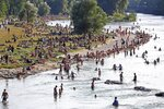 FILE - In this July 25, 2019 file photo people enjoy the hot summer weather at the river Isar in Munich, Germany. The world could see average global temperatures 1.5 degrees Celsius (2.7 Fahrenheit) above the pre-industrial average for the first time in the coming five years, the U.N. weather agency said Thursday. The 1.5-C mark is a key threshold that countries have agreed to limit global warming to, if possible. Scientists say average temperatures around the world are already at least 1 C higher now than during the period from 1850-1900 because of man-made greenhouse emissions. (AP Photo/Matthias Schrader, File)