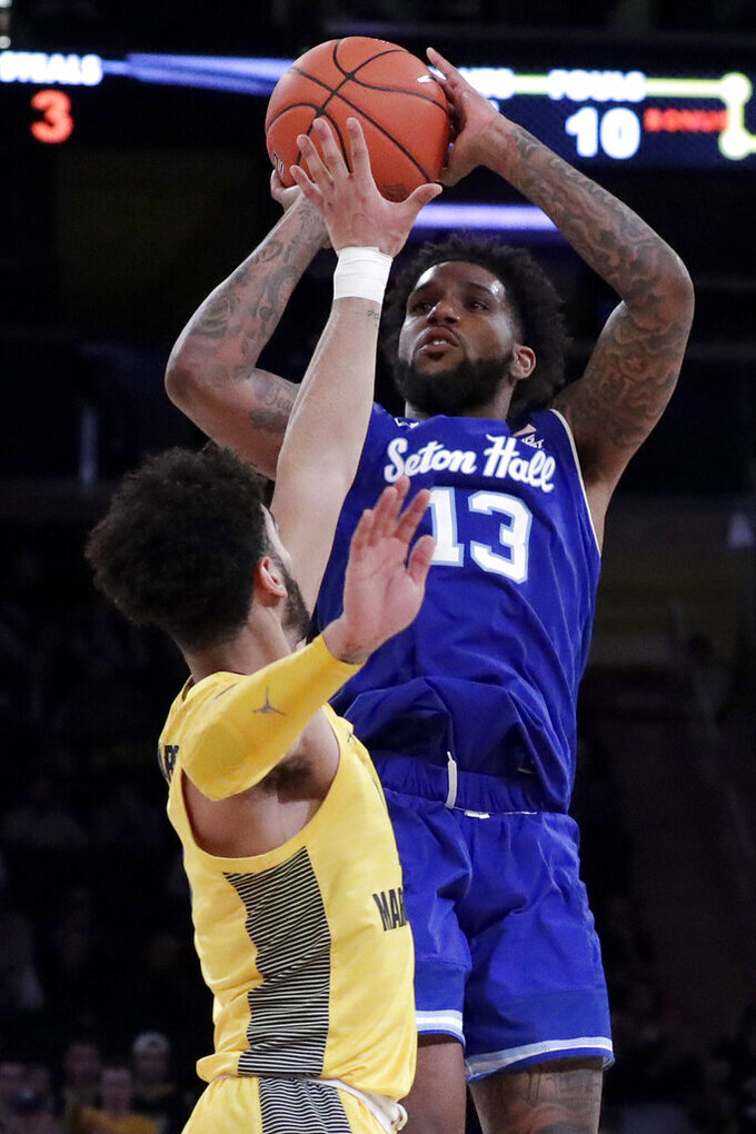 Seton Hall guard Myles Powell (13) shoots against Marquette guard Markus Howard during the second half of an NCAA college basketball semifinal game in the Big East men's tournament, Friday, March 15, 2019, in New York. Seton Hall won 81-79. (AP Photo/Julio Cortez)