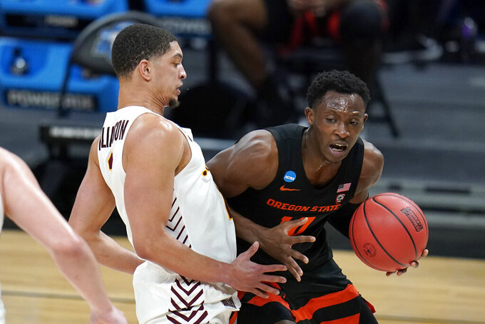 Oregon State forward Warith Alatishe, right, drives past Loyola Chicago guard Lucas Williamson, left, during the second half of a Sweet 16 game in the NCAA men's college basketball tournament at Bankers Life Fieldhouse, Saturday, March 27, 2021, in Indianapolis. (AP Photo/Jeff Roberson)