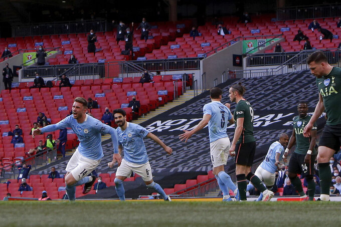 Manchester City's Aymeric Laporte, left, celebrates after scoring the opening goal during the English League Cup final soccer match between Manchester City and Tottenham Hotspur at Wembley stadium in London, Sunday, April 25, 2021. (AP Photo/Alastair Grant)