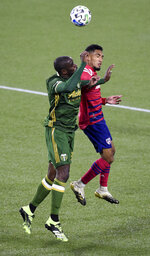 Portland Timbers defender Larrys Mabiala, left, and FC Dallas forward Jesus Ferreira go up for a ball during the first half of an MLS soccer match in Portland, Ore., Sunday, Nov. 22, 2020. (AP Photo/Steve Dykes)