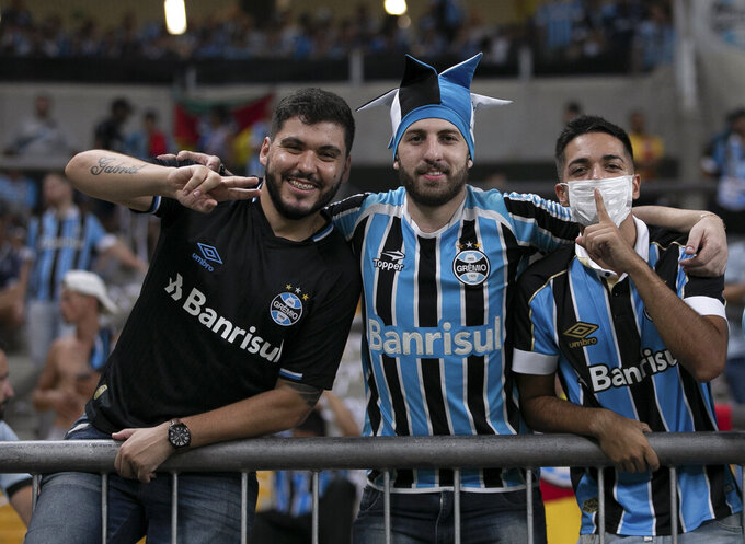 Fans of Brazil's Gremio pose for a photo prior to a Copa Libertadores soccer match against Internacional at Gremio Arena in Porto Alegre, Brazil, Thursday, March 12, 2020. (AP Photo/Liamara Polli)