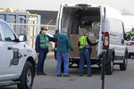 A Indiana State Police officer and IDOT employees check a pallets of medical supplies in the back of a truck, Thursday, March 26, 2020, in Indianapolis. The medical supplies were being delivered to Indiana hospitals and health departments to help fight the coronavirus pandemic.  (AP Photo/Darron Cummings)