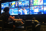 A gambler watches sporting events on large screens at the FanDuel sportsbook in East Rutherford N.J. on Aug. 30, 2021. The American Gaming Association says 45.2 million Americans plan to bet on NFL games this season, up 36% from last year. (AP Photo/Wayne Parry)