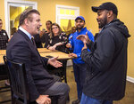 Actor Alec Baldwin speaks with Josh Cole, right, who is running for the Virginia House of Delegates 28th District, and Qasim Rashid, second right, running for Virginia's 28th District Senate seat, during a visit to the Leeland Station Clubhouse in Stafford County, Va., on Tuesday, Oct. 22, 2019. (Peter Cihelka/The Free Lance-Star via AP)