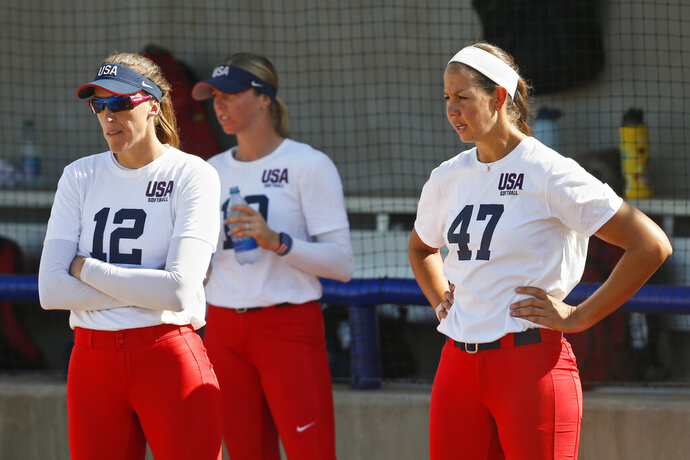 FILE - In this Oct. 2, 2019, file photo, pitchers Monica Abbott, left, and Cat Osterman, right, watch during the USA Softball Women's Olympic Team Selection Trials in Oklahoma City. The Scrap Yard Dawgs, one of America's top pro women's softball teams, continue to suffer fallout from a controversial post on the team's Twitter account. Dawgs players Cat Osterman and Monica Abbott, both members of Team USA, are among those who have criticized it. (AP Photo/Sue Ogrocki, File)