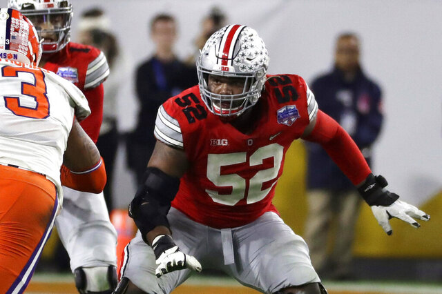 FILE - Ohio State offensive lineman Wyatt Davis (52) is shown during the first half of the Fiesta Bowl NCAA college football game against Clemson, Saturday, Dec. 28, 2019, in Glendale, Ariz. Two of Ohio State's biggest stars, Guard Wyatt Davis and cornerback Shaun Wade, have decided to stay and play football for the Buckeyes this year. (AP Photo/Rick Scuteri, File)