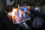 Iranian protesters burn a picture of French President Emmanuel Macron and President Donald Trump during a protest against Macron and the publishing of caricatures of the Prophet Muhammad they deem blasphemous, in front of French Embassy in Tehran, Iran, Wednesday, Oct. 28, 2020. (AP Photo/Ebrahim Noroozi)