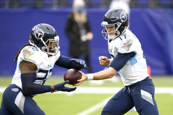 Tennessee Titans quarterback Ryan Tannehill, right, hands off to running back Derrick Henry during the first half of an NFL football game against the Baltimore Ravens, Sunday, Nov. 22, 2020, in Baltimore. (AP Photo/Nick Wass)