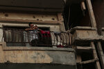 In this In this Thursday, Sept. 5, 2019, photo, a man uses his mobile phone on the balcony of a damaged apartment building in Raqqa, Syria. Two years after the military offensive to oust the Islamic State group from its stronghold, Raqqa has been picking up the pieces. While skeletons of tall hollowed buildings still dot the skyline, residents have moved in, some rebuilding partially destroyed apartments or opening shops at the bottom of others. (AP Photo/Maya Alleruzzo)