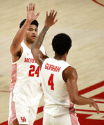 Houston guard Quentin Grimes (24) celebrates his three-point basket with Justin Gorham during the first half of an NCAA college basketball game against South Florida, Sunday, Feb. 28, 2021, in Houston. (AP Photo/Eric Christian Smith)