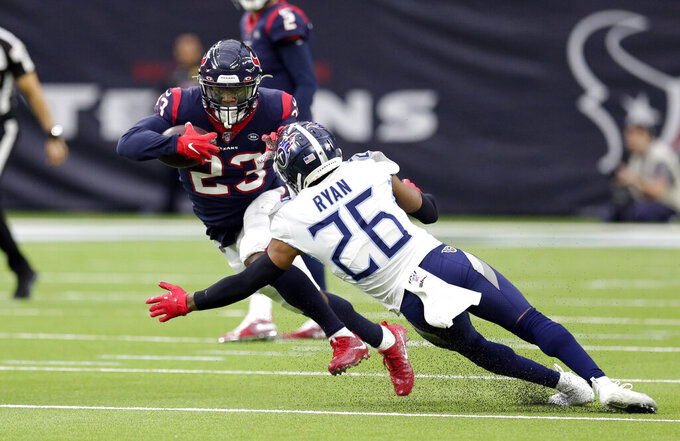 Houston Texans running back Carlos Hyde (23) rushes for a gain as Tennessee Titans cornerback Logan Ryan (26) reaches to tackle him during the first half of an NFL football game Sunday, Dec. 29, 2019, in Houston. (AP Photo/Michael Wyke)