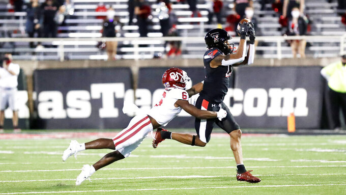 Texas Tech wide receiver Erik Ezukanma makes a reception while covered by Oklahoma cornerback Tre Brown in the first half of an NCAA college football game, Saturday, Oct. 31, 2020, in Lubbock, Texas. (AP Photo/Mark Rogers)
