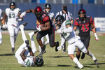 San Diego State running back Greg Bell, center, leaps over Hawaii defensive back Quentin Frazier, bottom left, during the first half of an NCAA college football game Saturday, Nov. 14, 2020, in Carson, Calif. (AP Photo/Kyusung Gong)