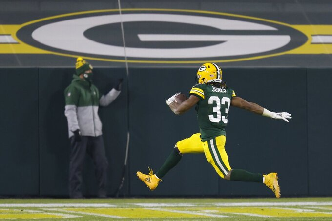 Green Bay Packers' Aaron Jones runs for a touchdown during the first half of an NFL football game against the Carolina Panthers Saturday, Dec. 19, 2020, in Green Bay, Wis. (AP Photo/Matt Ludtke)