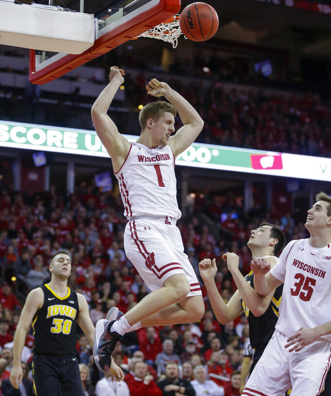 Wisconsin's Brevin Pritzl (1) dunks against Iowa's Connor McCaffery (30) and Ryan Kriener, second from right, during the second half of an NCAA college basketball game Thursday, March 7, 2019, in Madison, Wis. Wisconsin won 65-45. (AP Photo/Andy Manis)