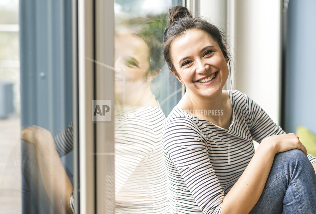 Portrait of happy woman sitting at the window at home