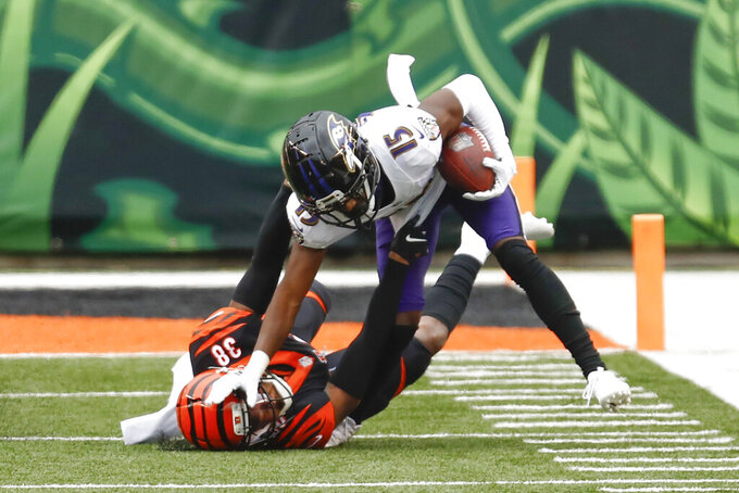 Baltimore Ravens' Marquise Brown (15) stiff-arms Cincinnati Bengals cornerback LeShaun Sims (38) to the ground as he returns punt during the first half of an NFL football game, Sunday, Jan. 3, 2021, in Cincinnati. (AP Photo/Aaron Doster)