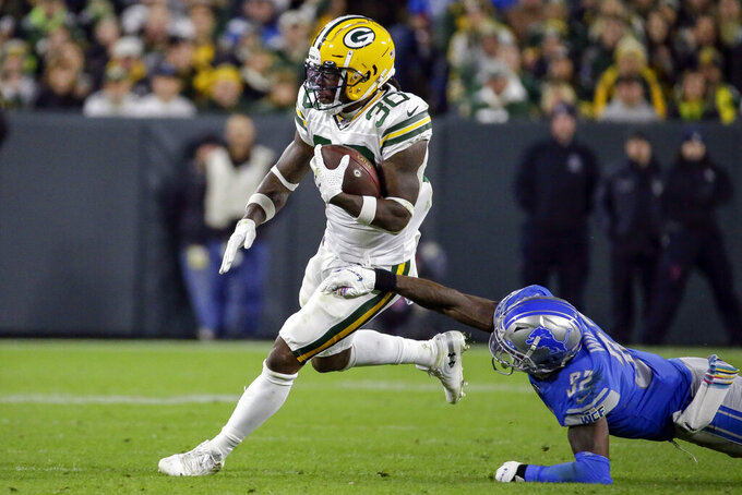 Green Bay Packers running back Jamaal Williams, left, breaks a tackle by Detroit Lions defensive back Tavon Wilson during the first half of an NFL football game Monday, Oct. 14, 2019, in Green Bay, Wis. (AP Photo/Mike Roemer)