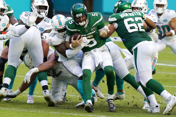 FILE - In this Oct. 18, 2020, file photo, New York Jets quarterback Joe Flacco (5) is sacked by Miami Dolphins linebacker Sam Eguavoen (49) during the first half of an NFL football game, Sunday,, in Miami Gardens, Fla. The Dolphins' run defense makes even Sunday's matchup against the New York Jets potentially problematic. The Jets are 0-10 and lost 24-0 at Miami in Week 6, but they're averaging a respectable 4.2 yards per carry and are sure to test the Dolphins' weakness. (AP Photo/Wilfredo Lee, File)
