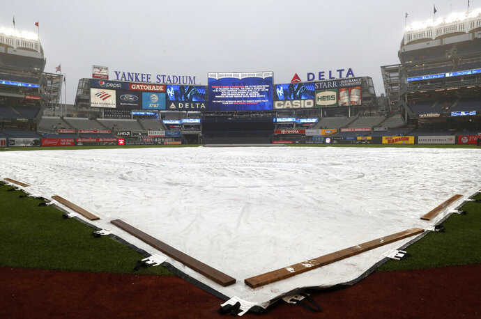 The field is covered by a tarp as rain falls before a baseball game between the New York Yankees and the New York Mets was postponed due to inclement weather, Monday, June 10, 2019, in New York. (AP Photo/Kathy Willens)