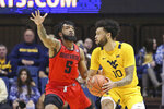 West Virginia guard Jermaine Haley (10) is defended by Austin Peay guard Jordyn Adams (5) as he goes to pass during the first half of an NCAA college basketball game Thursday, Dec. 12, 2019, in Morgantown, W.Va. (AP Photo/Kathleen Batten)