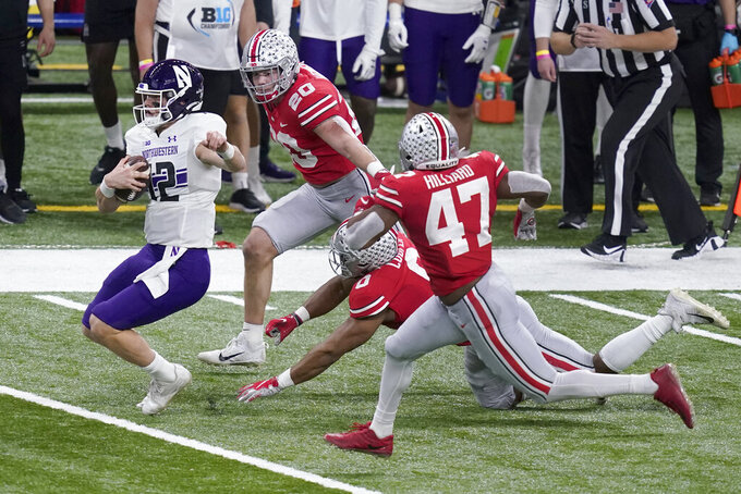 Northwestern quarterback Peyton Ramsey (12) scramble past Ohio State defenders Pete Werner (20), Jonathon Cooper (0) and Justin Hilliard (47) during the first half of the Big Ten championship NCAA college football game, Saturday, Dec. 19, 2020, in Indianapolis. (AP Photo/Darron Cummings)