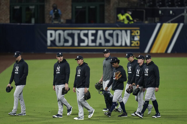 New York Yankees pitchers leave the field after the team's 2-1 loss to the Tampa Bay Rays in Game 5 of a baseball AL Division Series, Friday, Oct. 9, 2020, in San Diego. (AP Photo/Jae C. Hong)