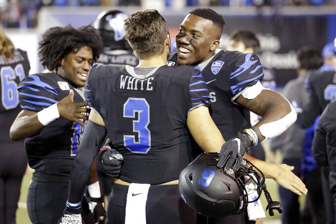 Memphis quarterback Brady White (3) hugs running back Patrick Taylor Jr. in the final minutes of the fourth quarter of an NCAA college football game against Cincinnati, Friday, Nov. 29, 2019, in Memphis, Tenn. (AP Photo/Mark Humphrey)