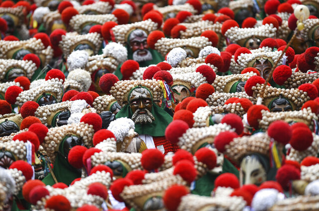 Hundreds of fools of the Elzacher Schuttig walk through the main street during the traditional Schuttig jump carnival parade in Elzach, Germany, Sunday, Feb 23, 2020. (Patrick Seeger/dpa via AP)