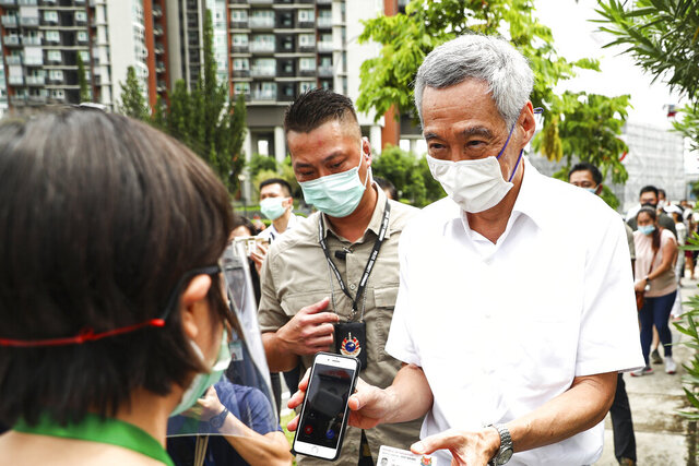 People's Action Party Secretary-General and Singaporean Prime Minister Lee Hsien Loong, right, verifies his identity with a polling official at the Alexandra Primary School polling center in Singapore, Friday, July 10, 2020. Wearing masks and plastic gloves, Singaporeans began voting in a general election that is expected to return Prime Minister Lee's long-governing party to power. (AP Photo)