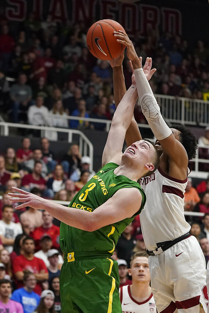 Oregon guard Payton Pritchard (3) has his shot blocked by Stanford guard Bryce Wills during the first half of an NCAA college basketball game Saturday, Feb. 1, 2020, in Stanford, Calif. (AP Photo/Tony Avelar)