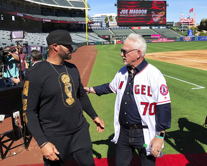 Los Angeles Angels first baseman Albert Pujols, left, speaks with new manager Joe Maddon after a baseball news conference at Angel Stadium in Anaheim, Calif., Thursday, Oct. 24, 2019. Maddon is returning to the Angels, where he worked as a coach before successful managerial stunts with baseball clubs in Tampa Bay and Chicago. (AP Photo/Greg Beacham)
