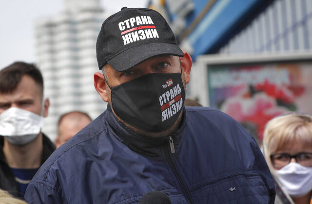 In this picture taken on Sunday, May 24, 2020, a blogger Sergei Tikhanovski, wearing a face mask to protect against coronavirus, speaks to people gathered to sign up and support potential presidential candidates in the upcoming presidential elections in Minsk, Belarus. The state Investigative Committee said Tuesday that Tikhanovski faces up to three years in prison on charges of violation of public order and assaulting a police officer during a protest against Belarusian President Alexander Lukashenko's re-election bid. (AP Photo/Sergei Grits)