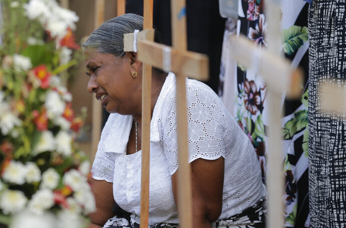 An elderly Sri Lankan woman cries sitting next to the grave of her family member who died in Easter Sunday church explosion in Katuwapitiya village in Negombo, Sri Lanka, Wednesday, April 24, 2019. Sri Lanka's president has asked for the resignations of the defense secretary and national police chief, a dramatic internal shake-up after security forces shrugged off intelligence reports warning of possible attacks before Easter bombings that killed over 350 people, the president's office said Wednesday. (AP Photo/Eranga Jayawardena)