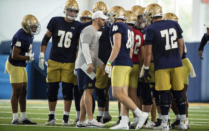 Notre Dame offensive coordinator Tommy Rees huddles with the offense during Notre Dame Fall Camp on Saturday, Aug. 7, 2021, at Irish Athletics Center in South Bend, Ind. (John Mersits/South Bend Tribune via AP)