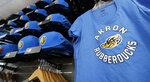 Akron RubberDucks logos show up on hat and shirt merchandise in the team shop before a minor league baseball game between Akron and Bowie, Thursday, April 18, 2019, in Akron, Ohio. Up in New England, there are yard goats. In the Deep South, there are spacebound raccoons. A wider scan of the American map reveals a menagerie of unlikely characters, from quarrelsome jumbo shrimp to aggrieved prairie dogs. (AP Photo/Tony Dejak)