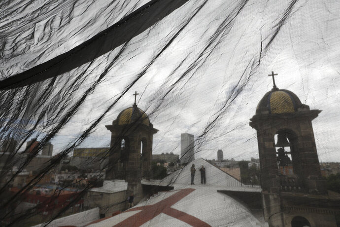 Men are seen through safety netting as they stand atop a less-damaged section of Nuestra Senora de Los Angeles, or Our Lady of Angels church, during the early stages of reconstruction work, three years after an earthquake collapsed nearly half of the church's 18th-century dome in Mexico City, Friday, Oct. 16, 2020. The experts working on projects like this across Mexico face some of the same issues confronting restorers everywhere, like France's re-building of the Notre Dame Cathedral: are the materials and craftsmen's skills of centuries ago still available? (AP Photo/Rebecca Blackwell)