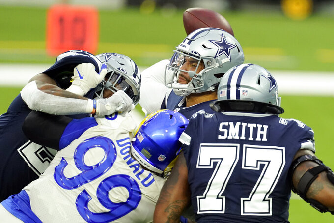 Dallas Cowboys quarterback Dak Prescott, top, throws under pressure from Los Angeles Rams defensive end Aaron Donald (99) during the first half of an NFL football game Sunday, Sept. 13, 2020, in Inglewood, Calif. (AP Photo/Ashley Landis )