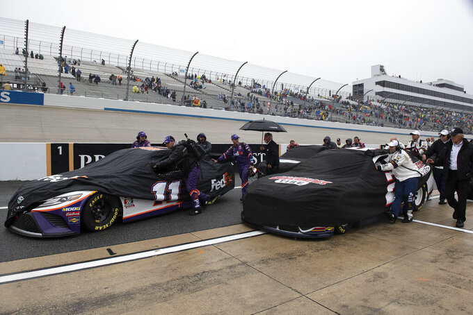 Teams push their cars down pit road after a NASCAR Cup Series auto race was postponed due to inclement weather conditions Sunday, May 5, 2019, at Dover International Speedway in Dover, Del. (AP Photo/Jason Minto)