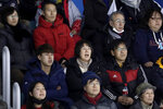 In a photo taken Monday, Feb. 12, 2018, Heo Saeng-gum, center, mother of South Korean player Kim Selin, reacts while sitting with her son Kim Se Hyung, left, and her husband Kim Woo Il, right, as they watch Kim Selin play for the Koreas during a women's hockey game against Sweden at the 2018 Winter Olympics in Gangneung, South Korea. Parents of players at Koreas' joint women's hockey team say they are so proud of their daughters for creating history in inter-Korean relations. (AP Photo/Julio Cortez)